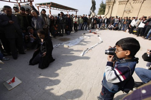 Hashim, 8, takes pictures of a man performing a mime at al-Mutanabi street in Baghdad